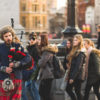 person playing bagpipes with crowd