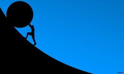 man pushing ball uphill
